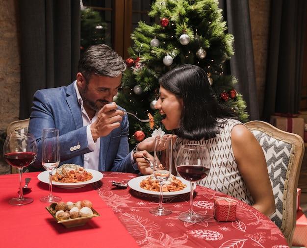 Leuke man en vrouw die kerstmisdiner hebben