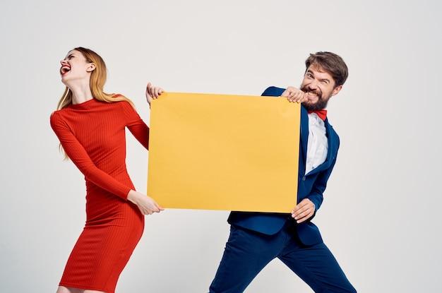 Leuke man en vrouw vasthouden aan gele mockup poster emoties kopiëren ruimte