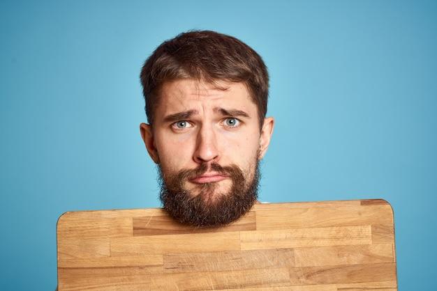 Leuke man met keukenbord dichtbij gezicht op blauw