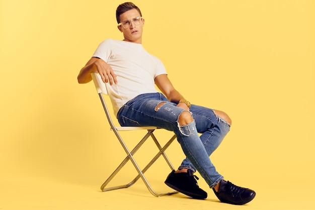 Leuke man zittend op een stoel witte t-shirt jeans levensstijl moderne stijl