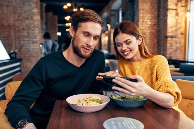 Leuke mannen en vrouwen in een restaurant met een telefoon in hun handen selfie