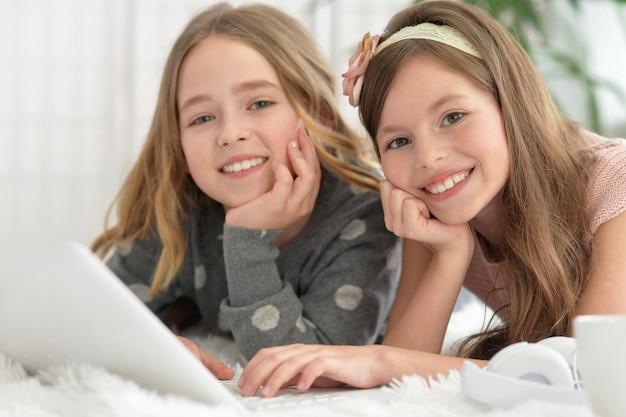 Leuke meiden binnen met laptop thuis