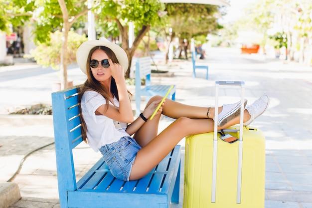Leuke meisje-reiziger zit op een blauwe bank met benen gestrekt op een gele koffer.