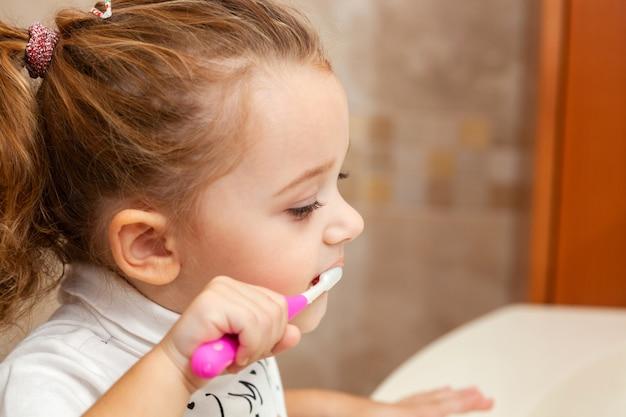 Leuke meisje schoonmakende tand met borstel.
