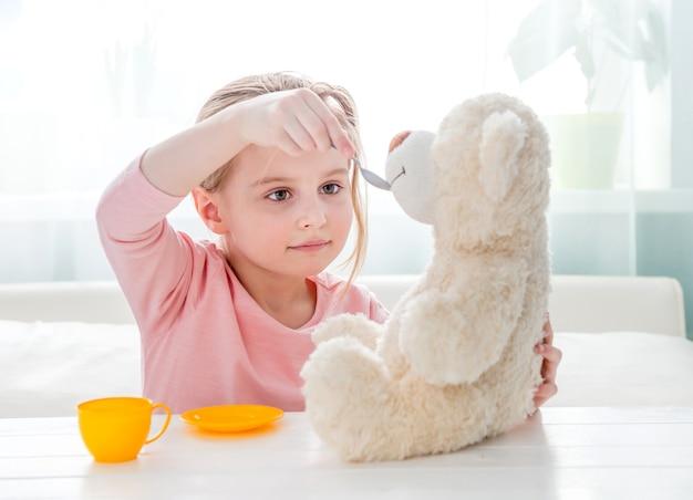 Leuke meisje voedende stuk speelgoed teddybeer