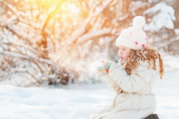 Leuke meisjes blazende sneeuw met haar hand, op een de wintergang in zonnige dag.
