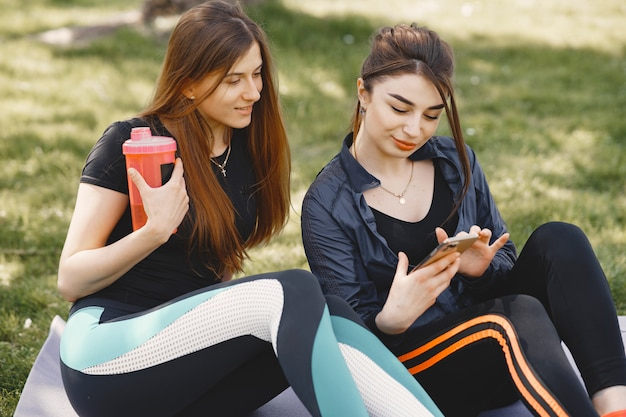 Leuke meisjes die yoga in een de zomerpark doen