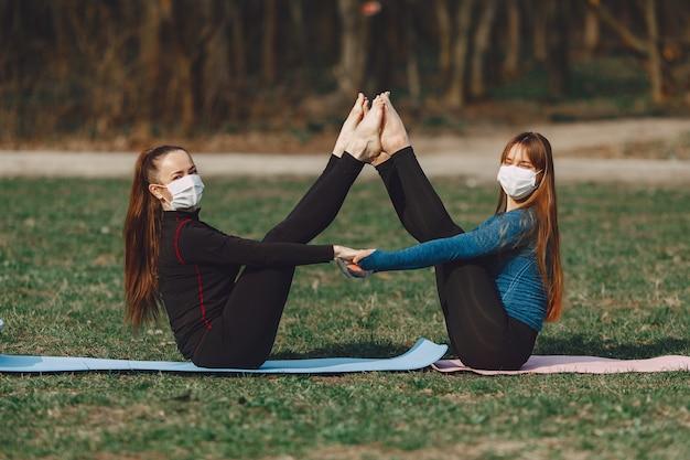 Leuke meisjes die yoga in maskers doen