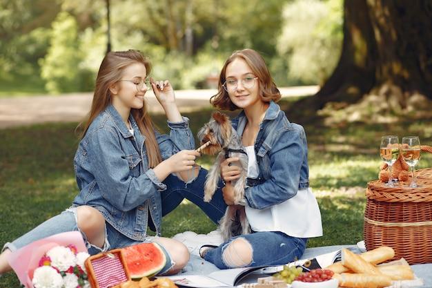 Leuke meisjes in een park spelen met kleine hond