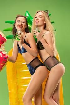 Leuke meisjes in zwembroek poseren in de studio en jus d'orange drinken