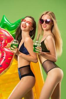 Leuke meisjes in zwembroek poseren in de studio en sinaasappelsap drinken
