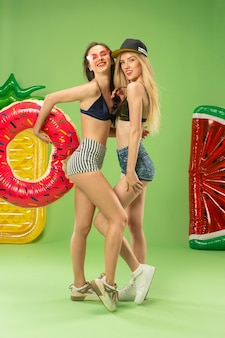 Leuke meisjes in zwembroek poseren in studio met opblaasbare cirkel zwemmen. zomer portret kaukasische tieners op groen