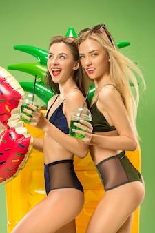 Leuke meisjes in zwemkleding poseren in de studio. zomer portret kaukasische tieners op groene achtergrond.