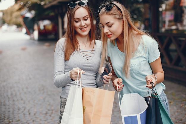 Leuke meisjes met boodschappentas in een stad