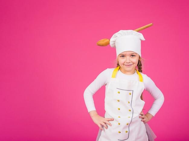 Leuke meisjeskok die zich met gietlepel op chef-kokshoed bevinden