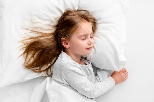 Leuke meisjesslaap vreedzaam in wit bed