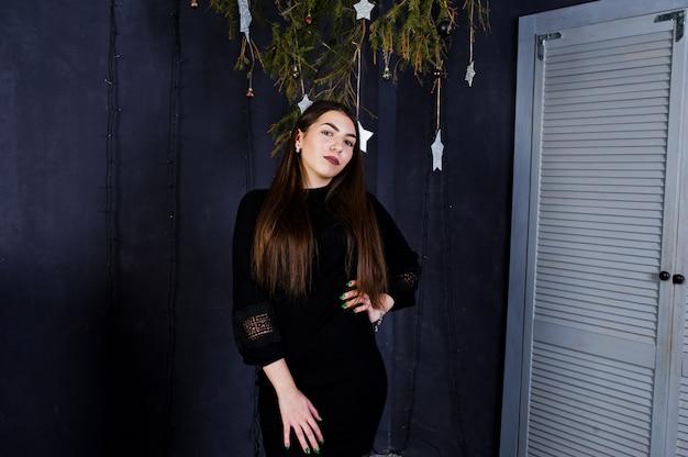 Leuke meisjesslijtage op zwarte kleding tegen kerstmisdecoratie.