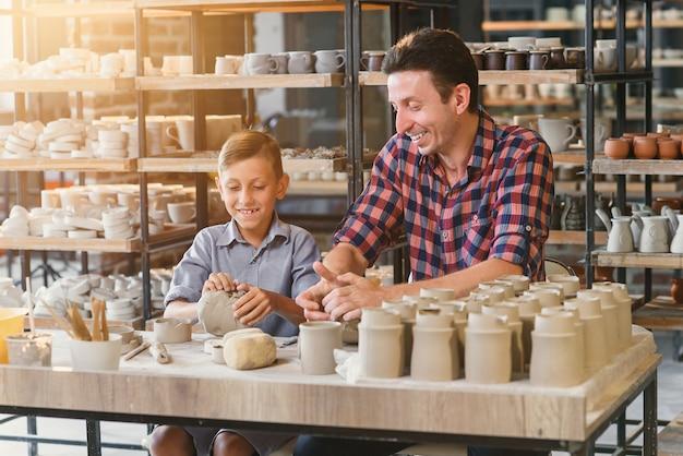 Leuke middelbare leeftijd man met zijn zoontje plezier in het aardewerk.