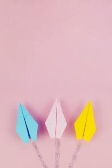 Leuke minimalistische papieren vliegtuigen met parcours op roze achtergrond