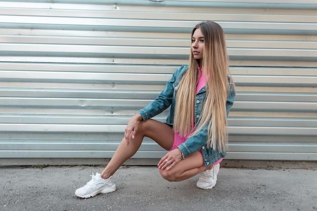 Leuke moderne jonge vrouw blonde in een modieuze denim jasje in trendy witte sneakers in een stijlvol roze sport pak zit in de buurt van zilveren muur op een zomerdag. glamour meisje model vormt buitenshuis.