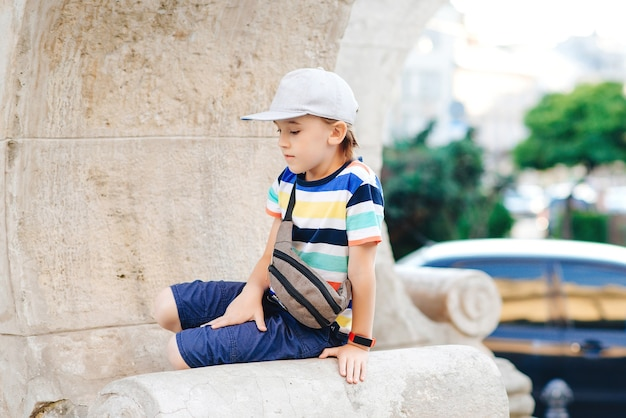 Leuke modieuze jongen die door de stad loopt. gelukkig kind dat trendy vrijetijdskleding en heuptas draagt. zomer mode. stijlvolle knappe jongen genieten van zomervakantie. gelukkige jeugd.