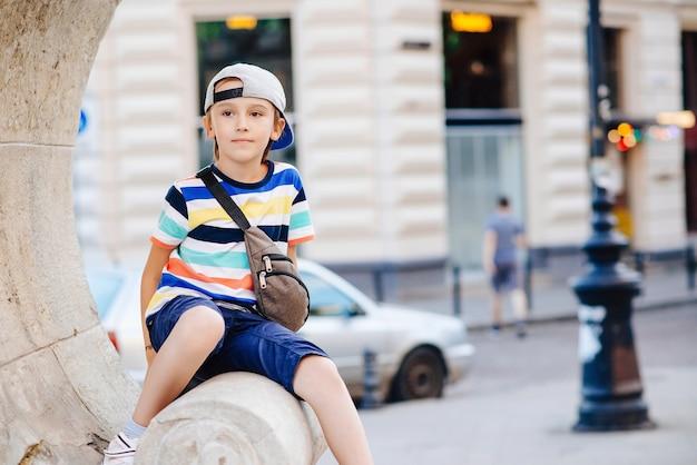 Leuke modieuze jongen die door de stad loopt. gelukkig kind dat trendy vrijetijdskleding en heuptas draagt.