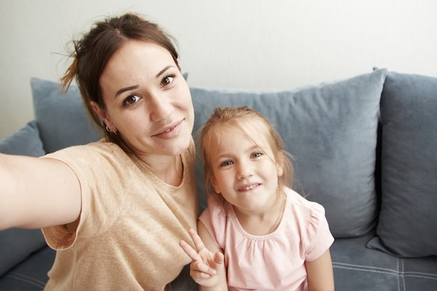 Leuke moeder en dochter nemen selfies en glimlachen naar de telefooncamera.
