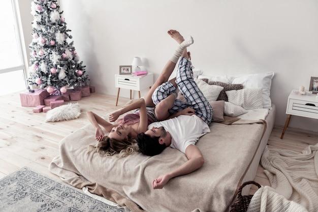 Leuke momenten. knappe bebaarde jonge man en zijn vrouw die witte dikke sokken dragen die van de ochtend genieten