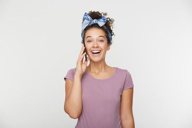 Leuke mooie aantrekkelijke brunette vrouw die met iemand aan de telefoon spreekt, ontvangt goed nieuws