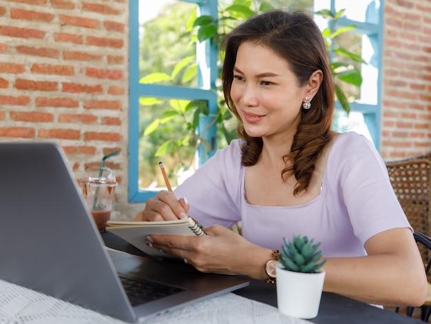 Leuke mooie aziatische vrouwenzitting van middelbare leeftijd in winkel en met behulp van een potlood om op een papieren notitieblok met een laptopcomputer te schrijven