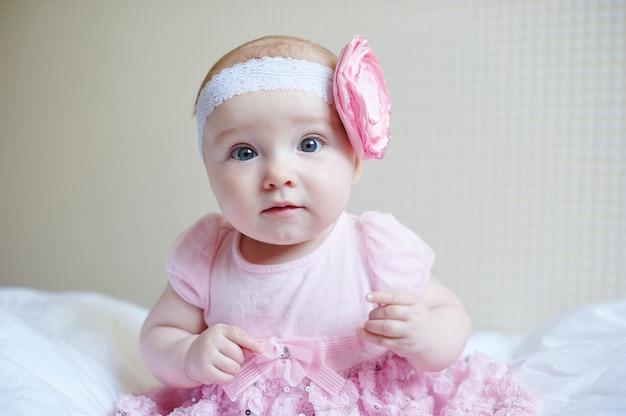 Leuke mooie babymeisje zittend op een bed in roze jurk