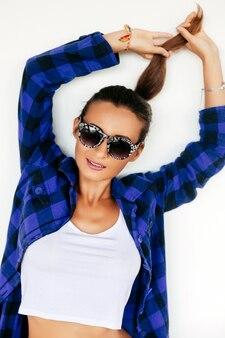 Leuke mooie jonge brunette vrouw plezier alleen lachend en spelen met haar haren in paardenstaart. witte achtergrond niet geïsoleerd.