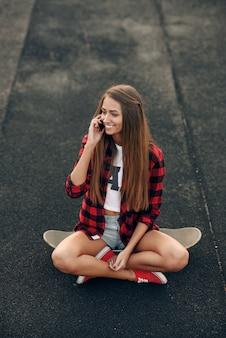 Leuke mooie jonge vrouw in een wit shirt, rood shirt, korte broek en sneakers, zittend op een skateboard en praten op de mobiele telefoon.