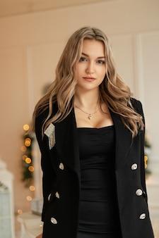 Leuke mooie jonge vrouw in modieus elegant zwart pak met blazer op avondfeest.
