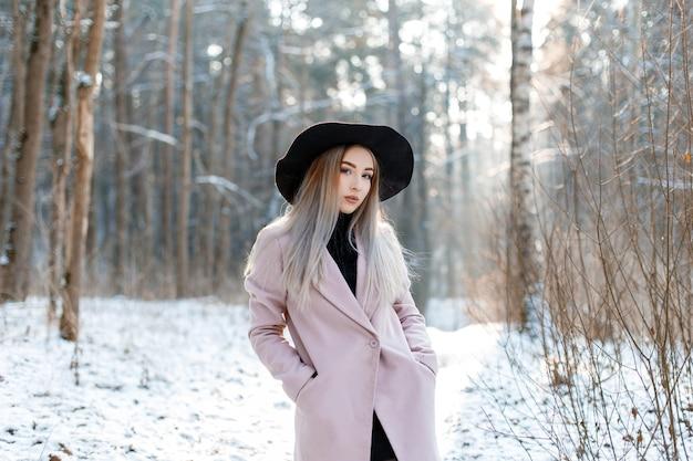 Leuke mooie jonge vrouw met blond haar in een vintage chique zwarte hoed in een roze elegante jas poseren in een winterpark. aantrekkelijk modieus meisje.