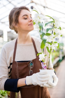 Leuke mooie jonge vrouwentuinman in bruine schort en tuinhandschoenen die and . houden