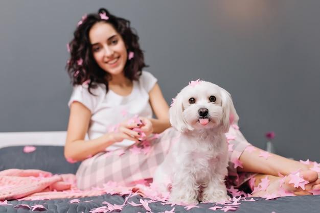 Leuke mooie kleine hond die tong op bed met vrij jonge vrouw toont. thuis chillen met huisdieren, grappige momenten