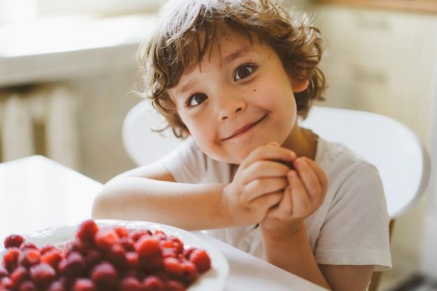 Leuke mooie kleine jongen die verse frambozen eet. gezonde voeding, jeugd en ontwikkeling.