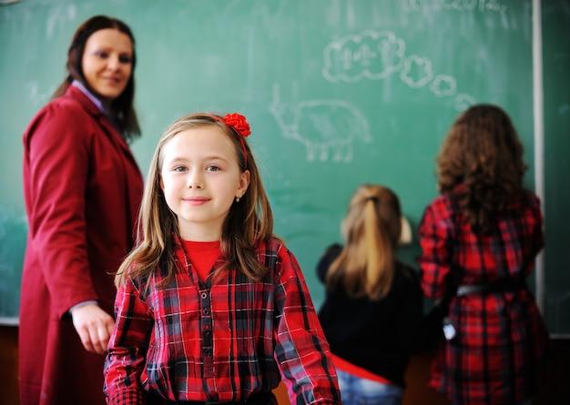 Leuke mooie schoolkinderen in klaslokaal die onderwijactiviteiten hebben