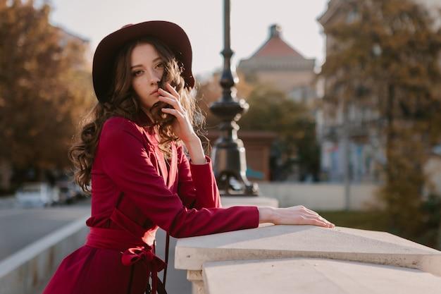Leuke mooie stijlvolle vrouw in paars pak wandelen in de stad straat, lente zomer herfst seizoen modetrend dragen hoed, portemonnee te houden