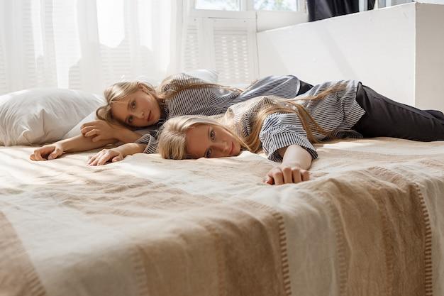 Leuke mooie tweelingzussen met lang blond haar in gestreepte shirts en zwarte broek liggen in bed bij zonnig