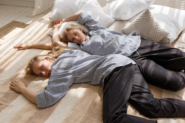 Leuke mooie tweelingzussen met lang blond haar in gestreepte shirts en zwarte broek liggen in bed in heldere zonnige studio