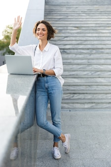 Leuke mooie vrouw buiten wandelen met behulp van laptopcomputer