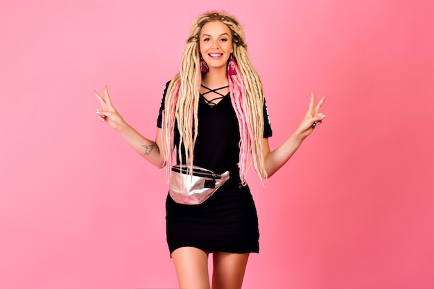 Leuke mooie vrouw, gekleed in casual outfit poseren op roze muur, stijlvol kapsel, positieve emoties.