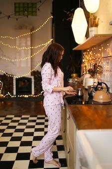 Leuke mooie vrouw in gezellige pyjama bereidt en maakt koffie in de keuken versierd met slingers