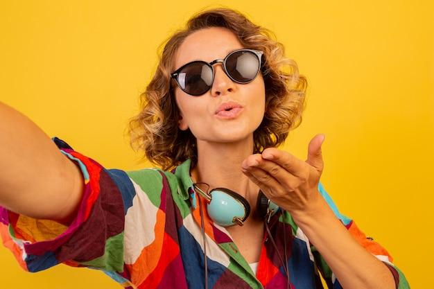 Leuke mooie vrouw met oortelefoons stuurt kus naar camera en maakt zelfportret over gele muur