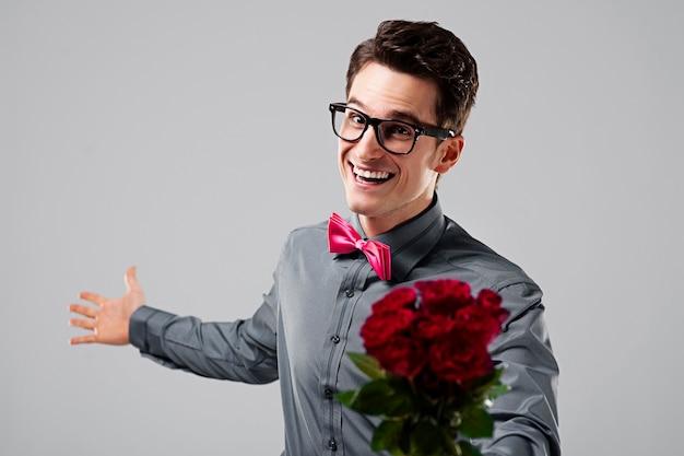 Leuke nerd met een boeket rozen