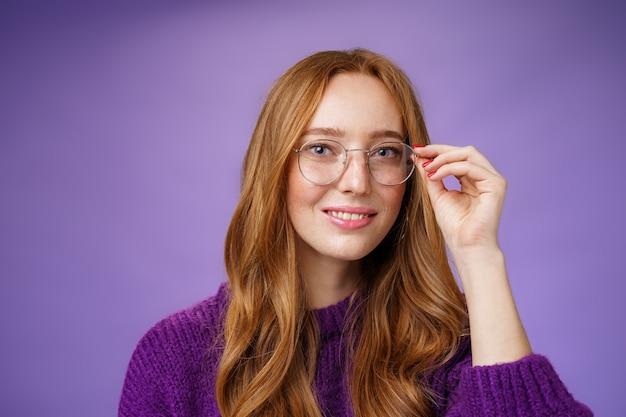 Leuke nerdy vrouwelijke student met natuurlijk mooi rood haar dat de rand van een bril aanraakt en veelbelovend en zelfverzekerd glimlacht naar de camera, gretig om te zien wat de toekomst in petto heeft na het afstuderen over paarse achtergrond.