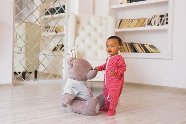 Leuke nieuwsgierige baby bestudeert dingen in de kamer.