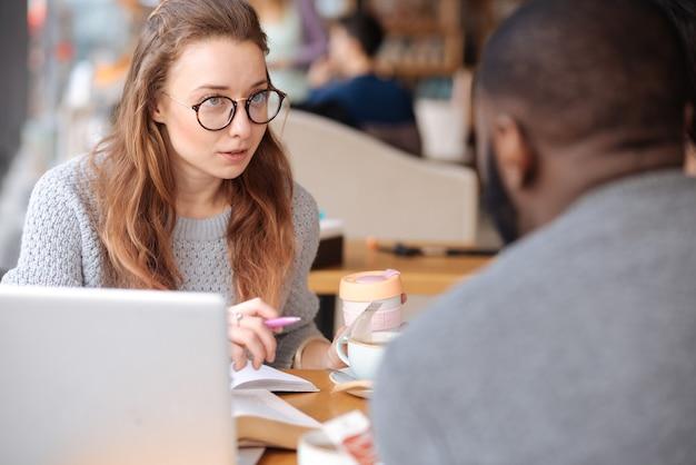 Leuke ontmoeting. vrij jong meisje scrollen nieuw op haar smartphone zittend in cafetaria onder andere internationale studenten.